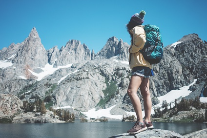 Woman with backpack trekking in snow mountain wilderness. Hipster hiking near stunning ice lake wearing funny pom hat